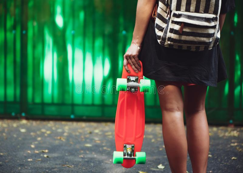Girl with plastic orange penny shortboard behind green wall in cap royalty free stock images
