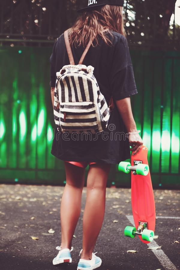 Girl with plastic orange penny shortboard behind green wall in cap stock photo