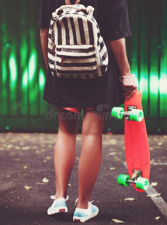 Girl with plastic orange penny shortboard behind green wall in cap stock images