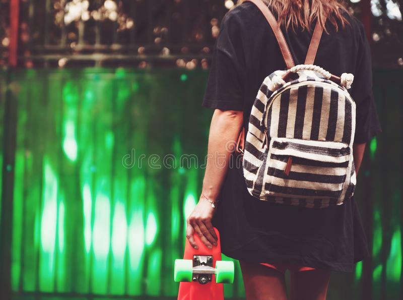 Girl with plastic orange penny shortboard behind green wall in cap royalty free stock image