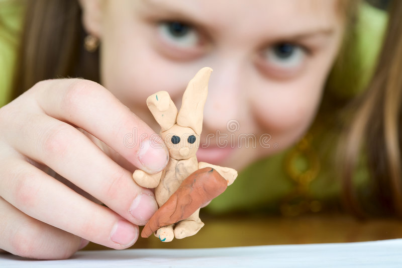 Girl with a plasticine rabbit royalty free stock photos