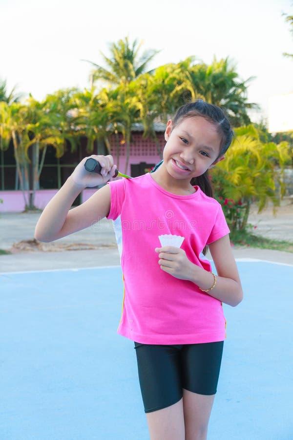 Girl play badminton. Cute little girl holding badminton racket and shuttlecock, Outdoor stock photography