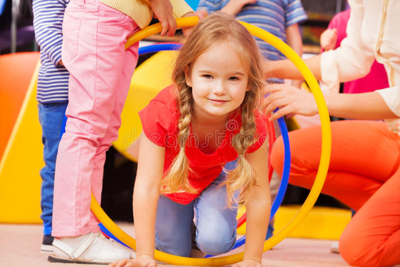 Girl play a game in kindergarten crawl though hoop royalty free stock photo