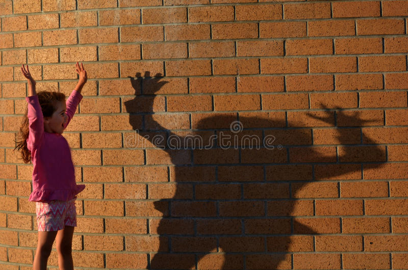 Girl play with her shadow stock images