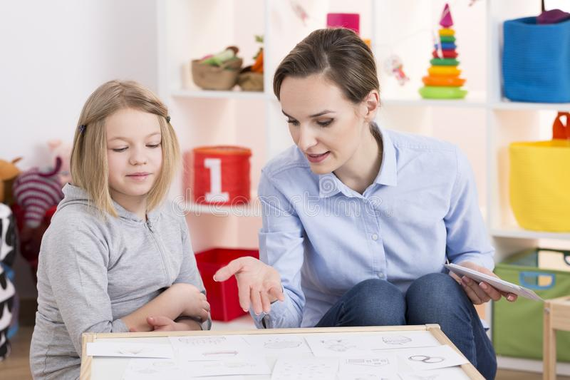 Girl during play therapy session. Young female therapist and little girl during play therapy session royalty free stock photos