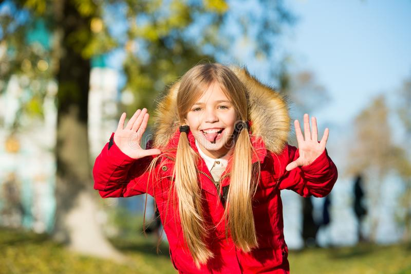 Girl playful grimace face in coat enjoy fall park. Playful kid leisure. Child blonde long hair walking in warm jacket royalty free stock photography