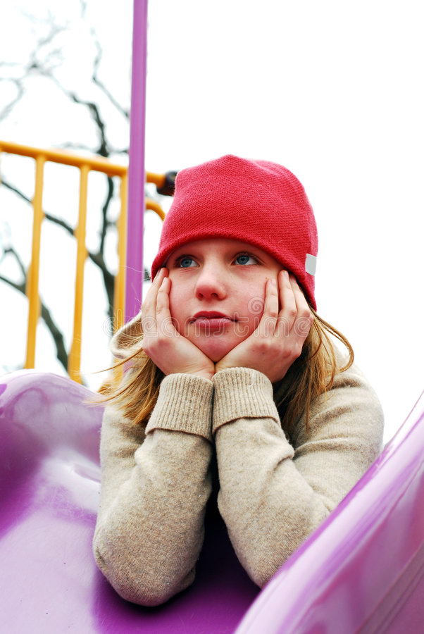 Girl on playground thinking. Young girl in a red hat on playground, thinking stock photography