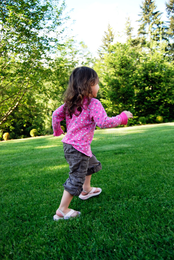 Girl Playing. Adorable brown-haired girl running in lush green grass on a summer day. Vertically framed shot stock images