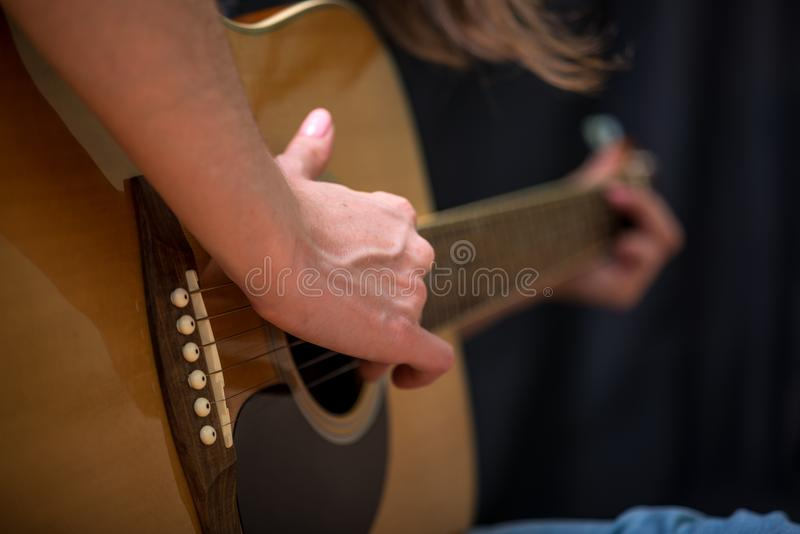 Girl playing an acoustic guitar on a dark background in the Studio. Concert young musicians. The girl playing an acoustic guitar on a dark background in the stock photo