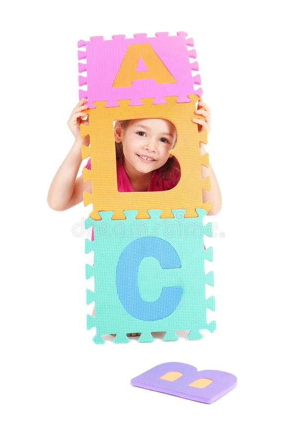 Girl playing with alphabet ABC. Young girl playing ABC alphabet letters. Isolated on white stock photography