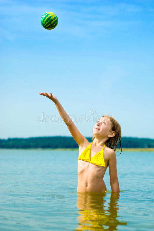 Download Girl Playing With Ball In Water Stock Photo - Image of lake, childhood: 15601112