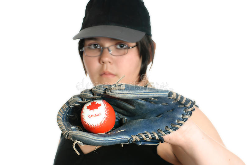Girl Playing Baseball. A young girl holding a Canadian baseball with a mitt, isolated against a white background stock photography