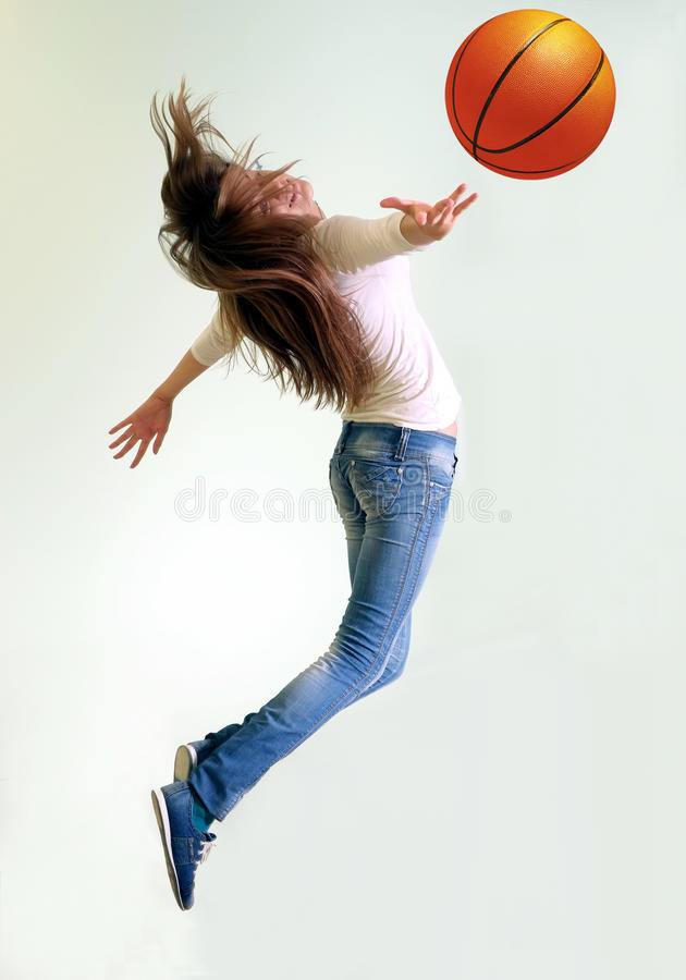 Girl playing basketball. A girl playing basketball jumping up royalty free stock photo
