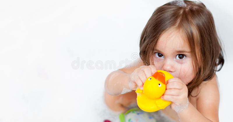 The girl playing in bath with foam. The child girl playing in bath with foam stock image