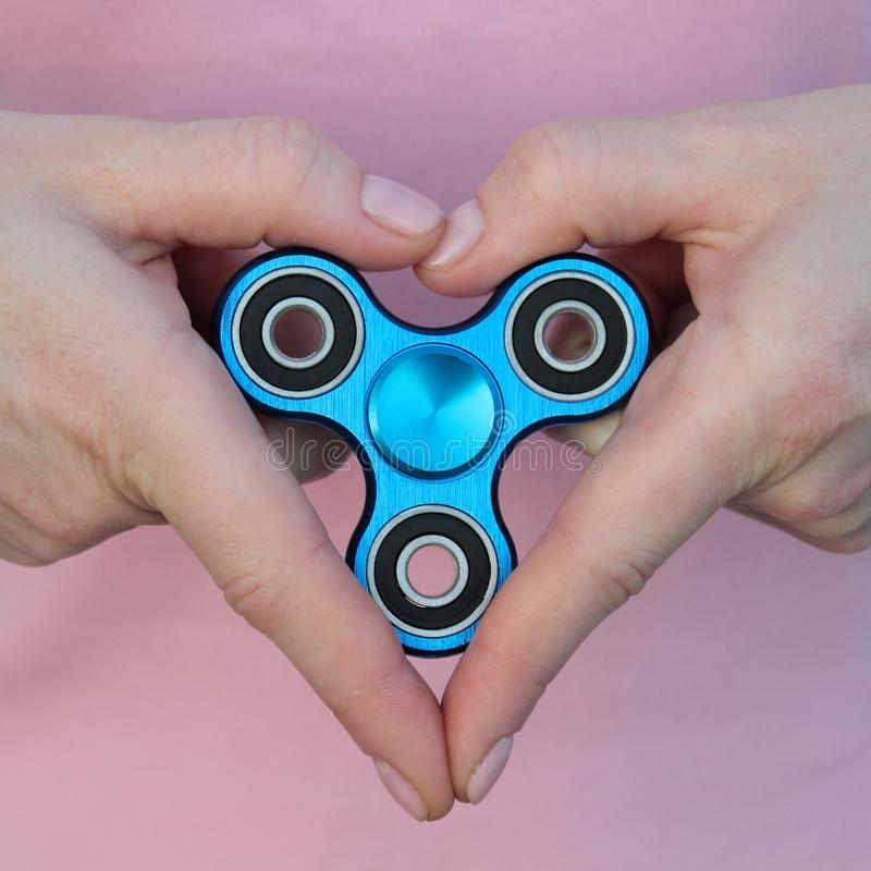 Girl is playing blue metal spinner in hands on the street, woman playing with a popular fidget spinner toy, girl love anxiety reli. Ef toy, anti stress and stock image