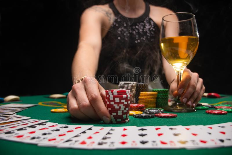 A girl playing in a casino raises bets with chips with a glass of wine. Gaming business.  stock photo