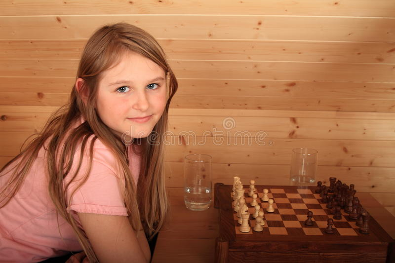Girl playing chess. Blond Caucasian kid - young hairy smiling girl sitting on armchair and playing chess in wooden attic room royalty free stock photo