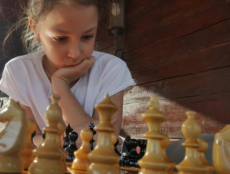 Girl playing chess. Young girl seriously studying chess board with wooden pieces stock photo