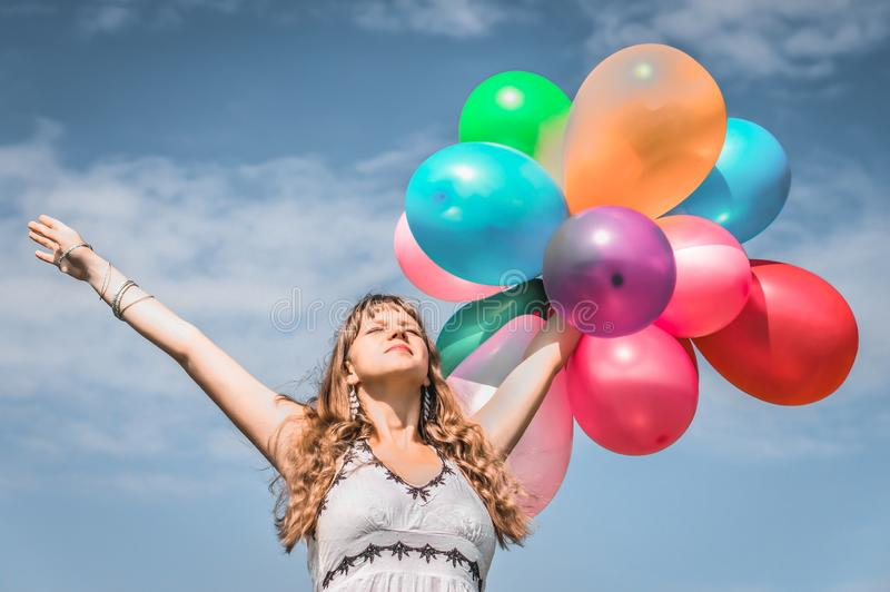 Girl playing with colorful balloons royalty free stock photography