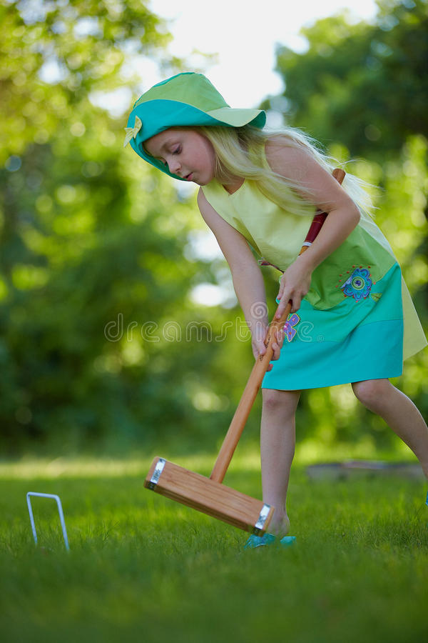 Girl playing croquet. Cute young girl playing croquet on grass lawn outdoors stock image
