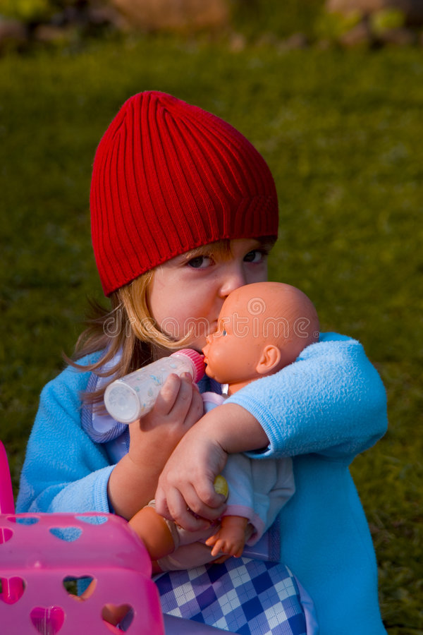 Girl playing with doll stock image