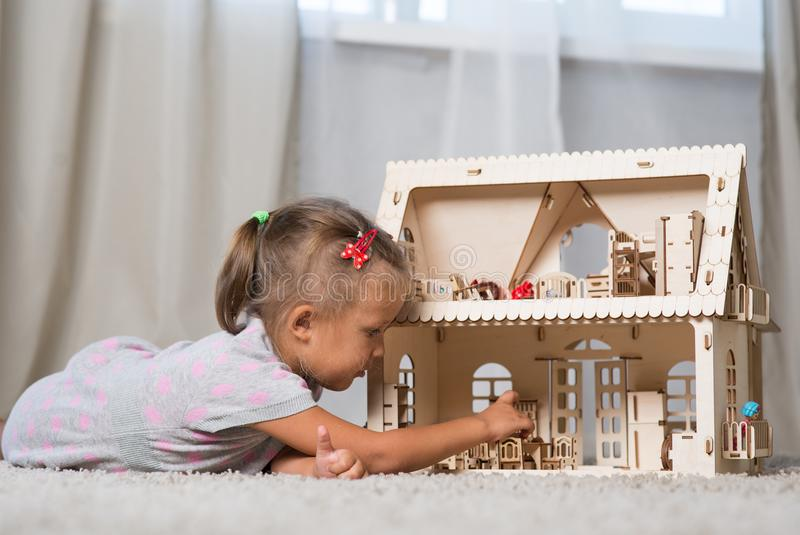 A girl playing with a dollhouse royalty free stock photography