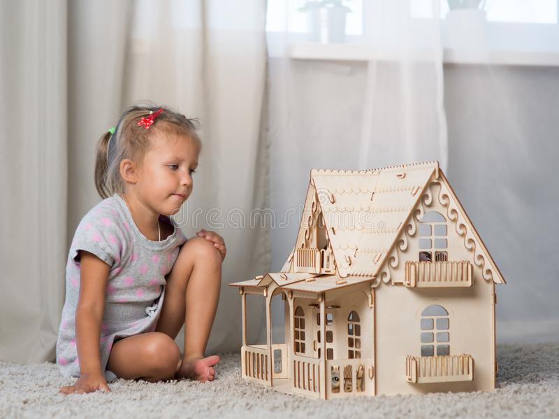 A girl playing with a dollhouse stock image