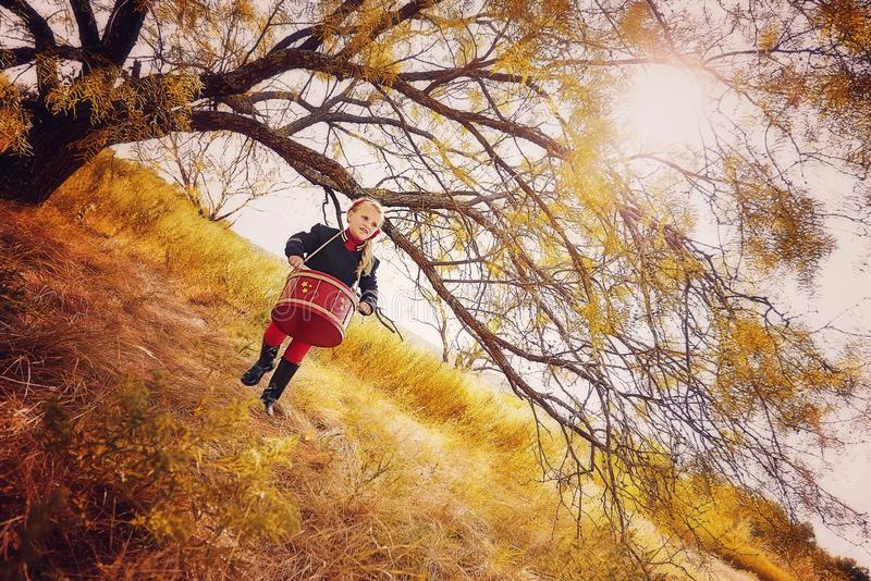 Girl playing drum. Little blonde girl walking under the branches of a big tree playing a red drum royalty free stock image
