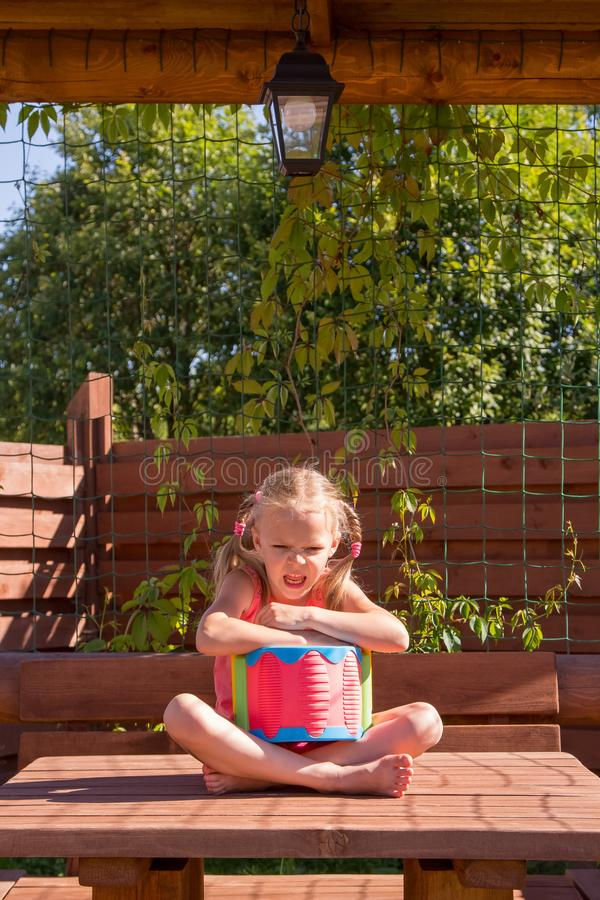 Girl playing with a drum in wooden arbor. Girl playing with a drum in a wooden arbor stock photos