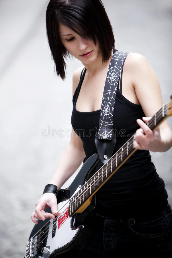 Girl playing electric bass stock photo