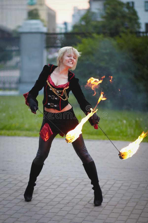 Girl playing with fire on fire show late at night. Fakir girl playing with fire on fire show royalty free stock image