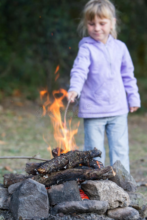 Girl playing with fire on natural background. Child girl playing with fire on natural background stock images