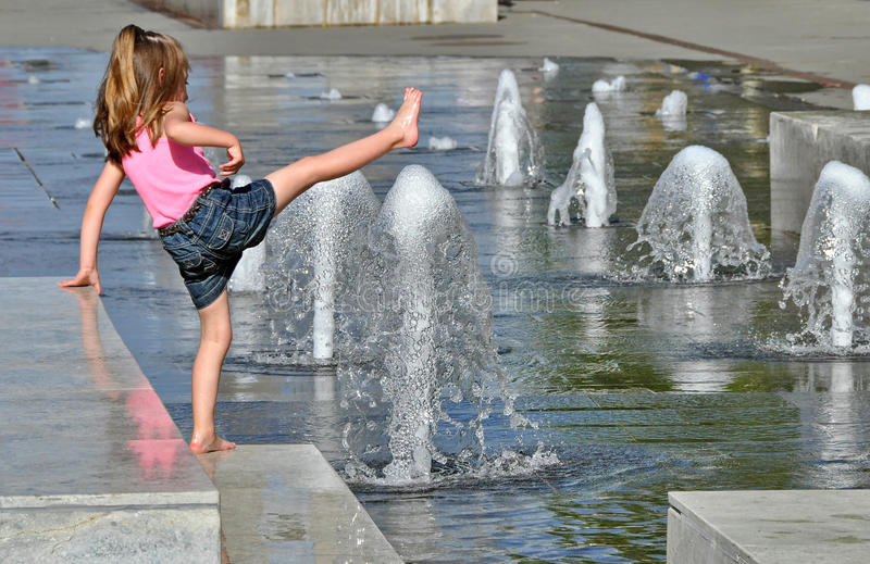 Girl Enjoys Water Fountain. Girl playing with water in park fountain in hot summer day stock photos