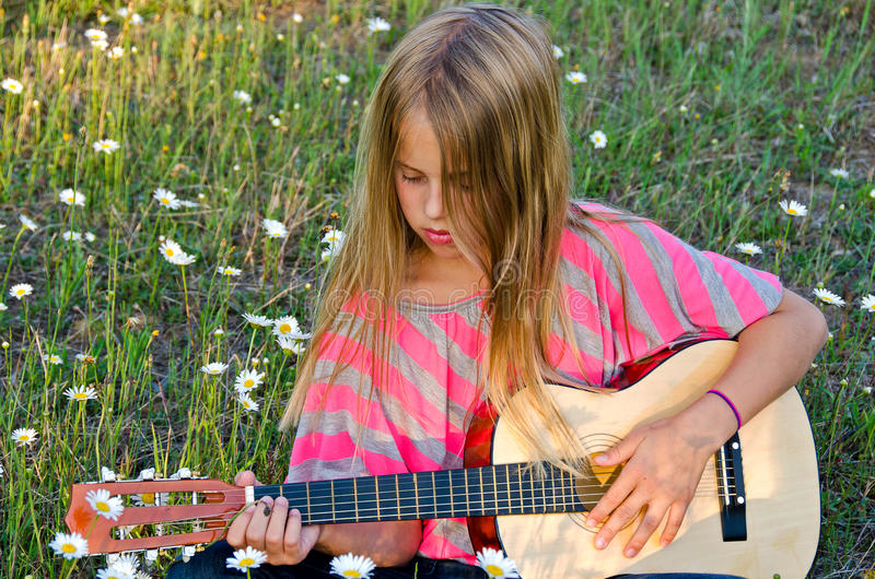Girl playing guitar stock images