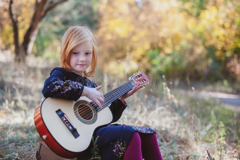 Girl playing guitar in the autumn forest royalty free stock photos