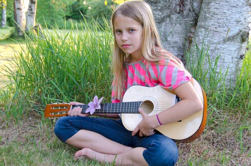 Girl playing guitar outdoors royalty free stock photos