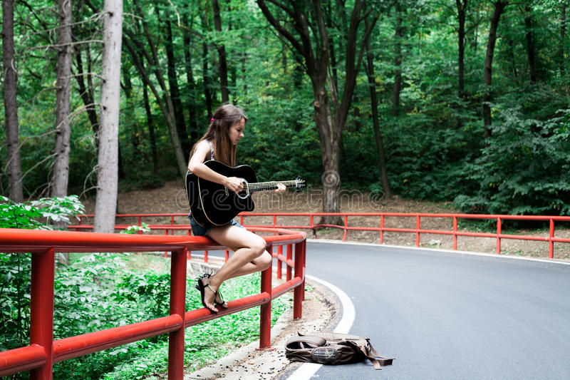 Girl playing guitar on a road side royalty free stock image