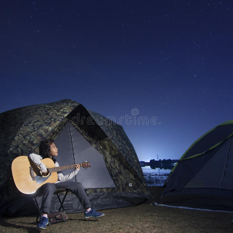 Girl playing guitar at tent glows under a night sky stock photo