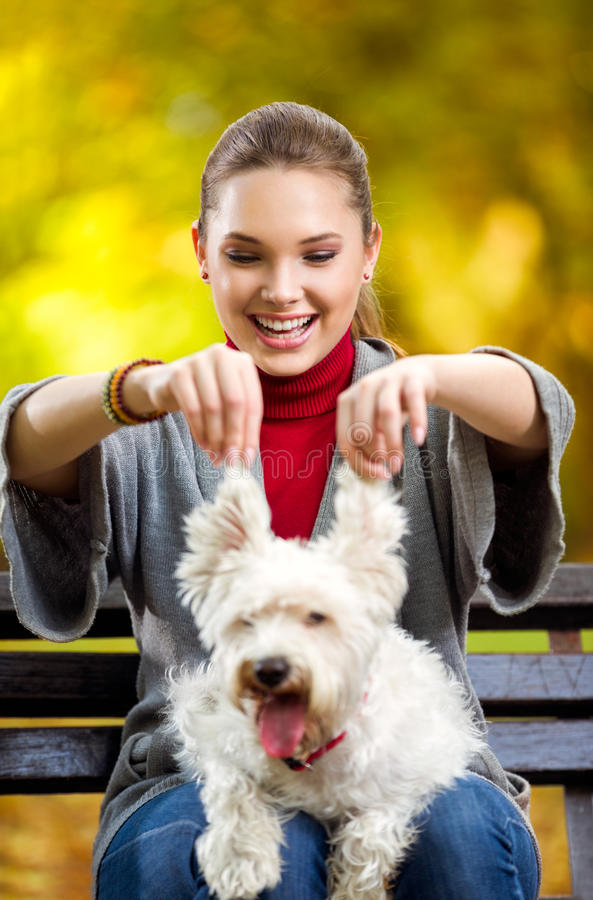 Girl playing with her funny dog. Funny young girl playing with her funny dog in autumn park stock image