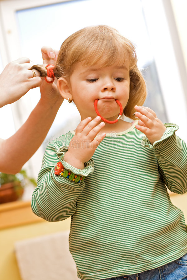 Girl playing during her morning beauty routine. Girl playing with rubber ring during her morning beauty routine stock photo
