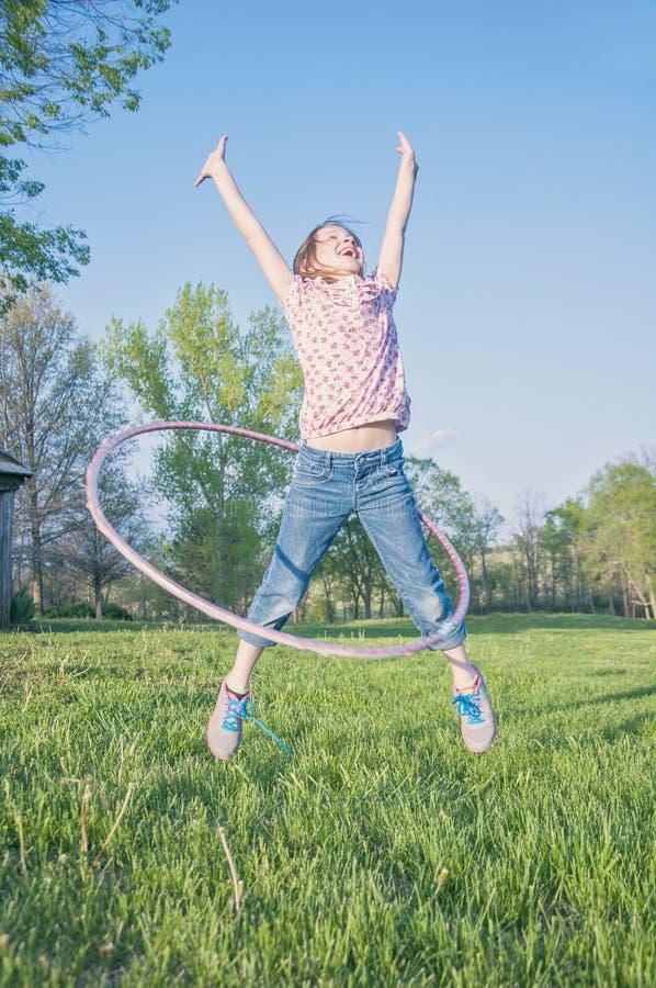 Girl playing hoola- hoop jumping. Ecstatic happy girl jumping with hula- hoop royalty free stock photography