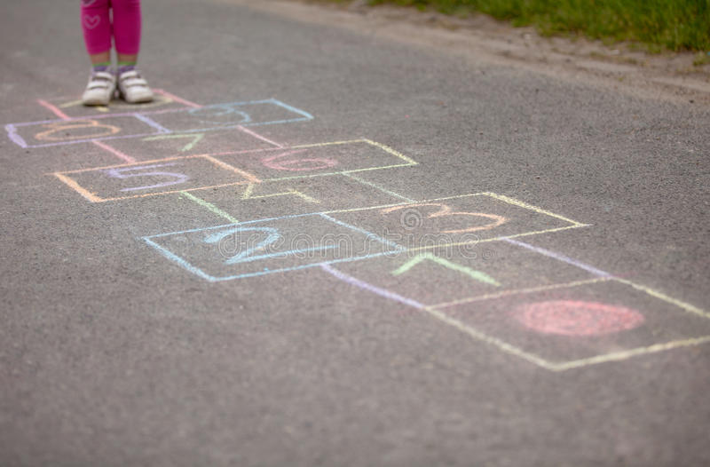 Girl playing hop-scotch outside royalty free stock photography