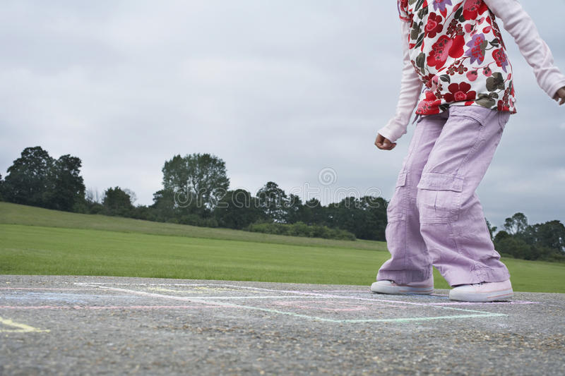 Girl Playing Hop-Scotch In Playground royalty free stock photography