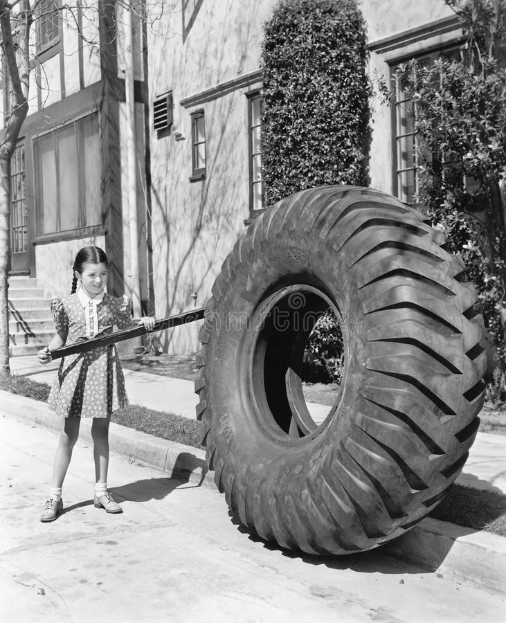 Girl playing with a huge tire and stick. (All persons depicted are no longer living and no estate exists. Supplier grants that there will be no model release stock photos
