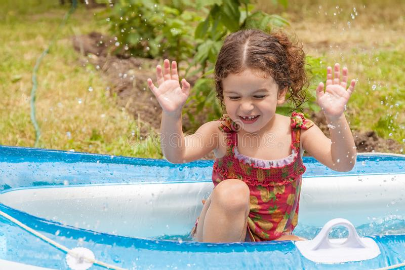 Girl playing in inflatable boat with water. Baby girl playing in an inflatable boat full of water royalty free stock images