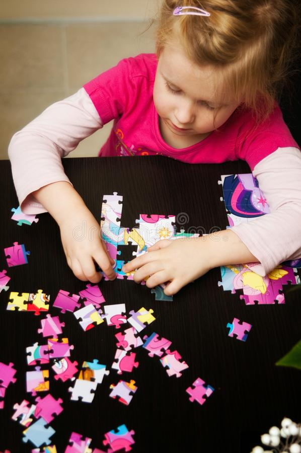 Girl playing with jigsaw puzzle. A cute young girl (four year old) playing with jigsaw puzzle while sitting at table at home royalty free stock photos