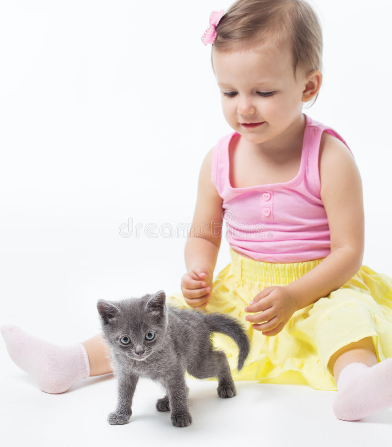 Girl playing with a kitten stock photos