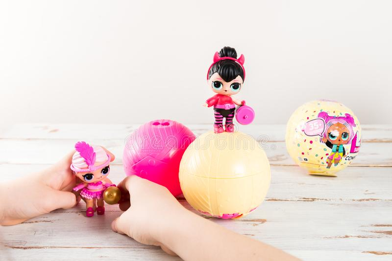 The girl is playing with L.O.L. Surprise Dolls stock image