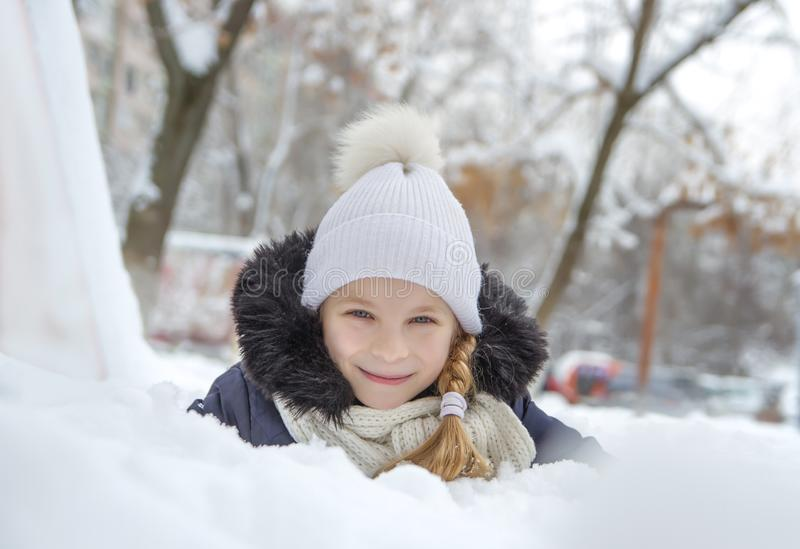 Girl playing lying in snow at winter park stock photography