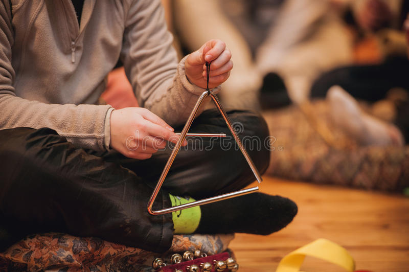 Girl playing a musical triangle. No face royalty free stock image